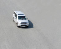 White SUV driving outside. A large, white, SUV driving outside on  the pavement Royalty Free Stock Photos