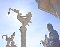 White stucco lamp in front of the temple with a statue of Guan Yin. royalty free stock photo