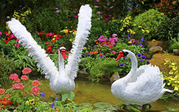White swans decoy in spring garden. Beautiful pair of white swans decoy in spring garden royalty free stock photography