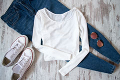 White sweatshirt, jeans, sneakers and glasses on a wooden background. Fashionable concept Stock Image