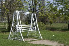 White swing in a green park. White wooden swing outdoor. Royalty Free Stock Images