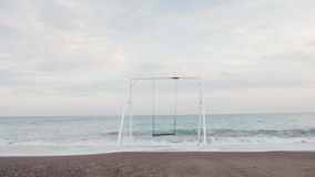 White swing near sea shaking at sunset . Vacation concept stock video
