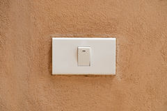 White switch on brown cement wall background. New white switch on brown cement wall background Stock Image