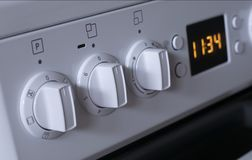 Handles of adjustment of power of heating of the electric stove. White switch power adjustment on the electric stove close-up Royalty Free Stock Image