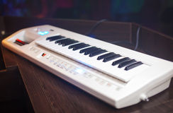 White synthesizer with black buttons on the table Royalty Free Stock Images