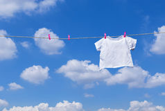 White T- shirt hanging on clothes line. Plain white T- shirt hanging on clothes line against blue sky stock image