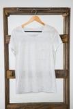White t-shirt hanging on wooden frame Stock Image