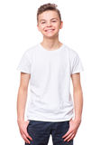 White t-shirt on teen boy. Handsome caucasian smiling child, isolated on a white background. Concept of childhood and fashion or advertisement design. Mock up royalty free stock images