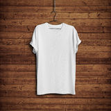 White t-shirt on wood wall. White blank t-shirt on dark wood wall royalty free stock photography