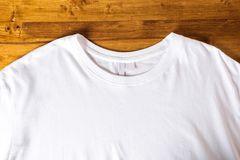 White t-shirt on a wooden background royalty free stock image
