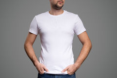 White t-shirt on a young man template. Gray background. White t-shirt on a young man template Royalty Free Stock Images