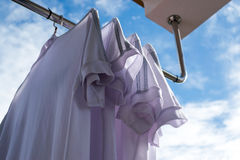 White T-shirts on clothesline against blue sky. Stock Photography