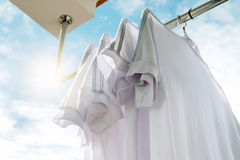 White T-shirts on clothesline against blue sky. Royalty Free Stock Photo
