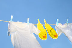 White t-shirts and slippers on the clothesline. On a sunny day royalty free stock photography