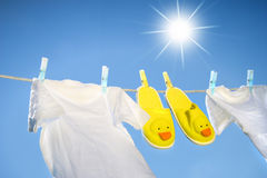 White t-shirts and slippers on the clothesline. On a sunny day stock image
