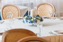White table blue flowers candle decoration. White table candle blue flowers  arrangement decoration interior Royalty Free Stock Images
