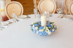 White table blue flowers candle decoration. White table candle blue flowers  arrangement decoration interior Stock Image
