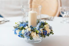 White table blue flowers candle decoration. White table candle blue flowers  arrangement decoration interior Royalty Free Stock Photography