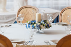 White table blue flowers candle decoration. White table candle blue flowers  arrangement decoration interior Royalty Free Stock Image