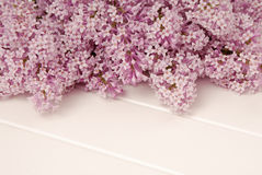 White table and bouquet of lilac, texturing backgroun Stock Image