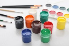 On a white table are brushes, watercolor paints and gouache royalty free stock image