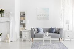 White table on carpet in front of grey settee in apartment interior with painting and lamp. Real photo. White table on carpet in front of grey settee in stock photos