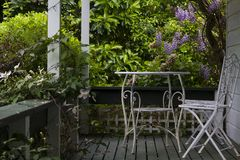 White table and chair on porch, and Tree  with purple flowers. White table and chair on porch, and Tree with purple flowers n Royalty Free Stock Photos