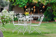 White table and chairs in beautiful garden, outdoo Stock Image