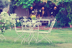 White table and chairs in beautiful garden. Vintage style pictur Royalty Free Stock Images