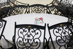 White table and chairs in the cafe with flowers Royalty Free Stock Photos
