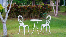 White table and chairs  in a garden Royalty Free Stock Images