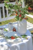 White table with coffee, caneles and flowers served in the garden stock photo