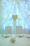 White table decor for the newlyweds in the restaurant. Backlight. Heart drapery Royalty Free Stock Photography