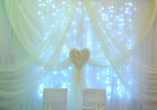 White table decor for the newlyweds in the restaurant. Backlight. Heart drapery Stock Photo