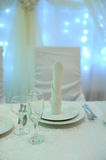 White table decor for the newlyweds in the restaurant. Backlight. Heart drapery Royalty Free Stock Image