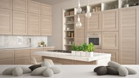 White table, desk or shelf with five soft white pillows in the shape of stars or flowers, over blurred modern wooden kitchen,. White architecture interior stock images