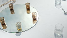 White table with drinks on mirror for banquet on fresh air outdoors. On light tablecloth decorating with glass reflection of sun, dishes, pearl long beads stock video footage