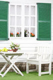 White table with fruits and flowers, chair near house Royalty Free Stock Images
