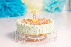 First celebration cake, one year old child - Smash the cake party. A white table holding a birthday cake for a 1 year old child. Cake is round and white, has a stock photography