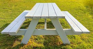 White table and picnic benches on green grass lawn glade. picnic area stock images