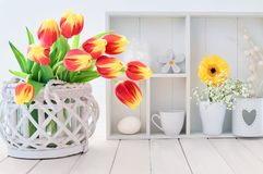 White table with red and yellow tulips and springtime decoration Stock Image