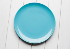 White table setting from above. Empty blue plate on planked wood .