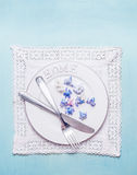 White table setting with Home plate, cutlery, lace doily napkin  and petal  flowers on blue shabby chic wooden background Royalty Free Stock Images