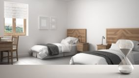 White table or shelf with crystal hourglass measuring the passing time over blurred modern bedroom with single beds, architecture. Interior design, copy space royalty free stock photos
