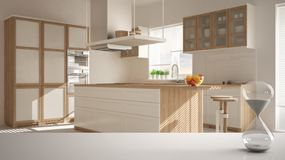 White table or shelf with crystal hourglass measuring the passing time over blurred wooden modern kitchen, architecture interior d. Esign, copy space background stock photo