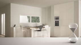 White table or shelf with crystal hourglass measuring the passing time over minimalist white kitchen with dining table,. Architecture interior design, copy royalty free illustration