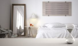 White table or shelf with crystal hourglass measuring the passing time over modern bedroom with double bed, architecture interior. Design, copy space background stock photography