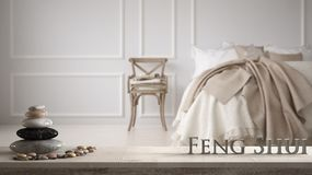 White table shelf with pebble balance and 3d letters making the word feng shui over evintage classic bedroom with soft bed full of. Pillows and blankets, zen royalty free stock images