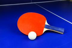 White Table Tennis Ball and a Red Racket on a Blue Table Royalty Free Stock Images