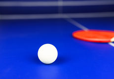 White Table Tennis Ball and a Red Racket on a Blue Table Royalty Free Stock Photos